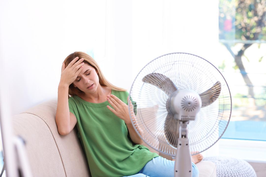 Lady sweating by fan